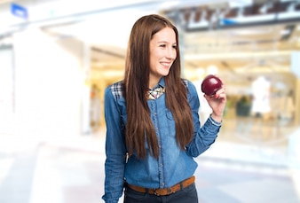 Trendy young woman holding a red apple and smiling