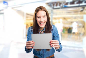 Trendy young woman looking happy holding a grey card