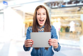 Trendy young woman looking surprised and holding a grey card