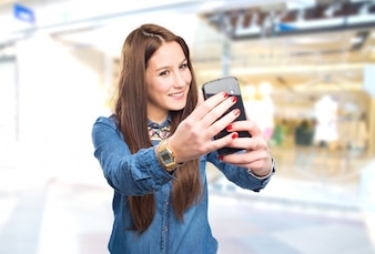 Trendy young woman taking a selfie with a smart phone