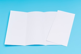 Trifold white template paper on blue background .
