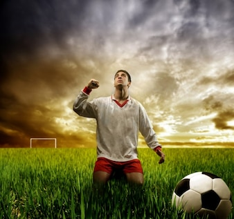 Triumphant footbal player on grass