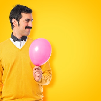 Twin brothers with balloons on colorful background