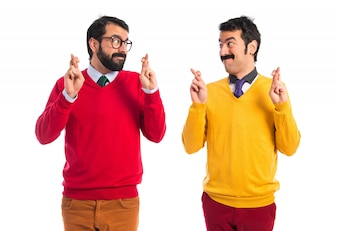 Twin brothers with fingers crossing