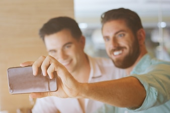 Two attractive men are taking a selfie with a smartphone