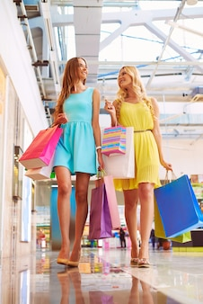 Two beautiful women walking down the mall after shopping