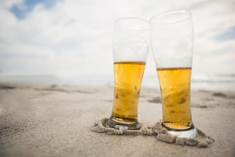 Two beer glasses kept on sand