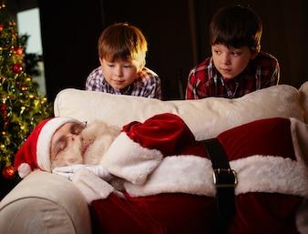 Two boys looking at santa asleep