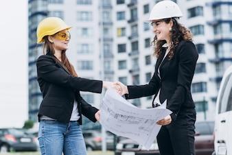 建築スキーム、建築コンセプトを見て保護ヘルメットと安全メガネの2つのビジネス女性