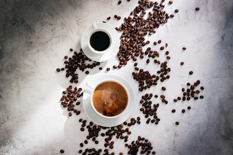 Two cups of coffee viewed from above and coffee beans around