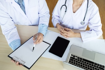 Two doctors discussing patient notes in an office pointing to a clipboard with paperwork as they make a diagnosis or decide on treatment