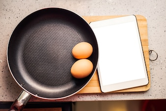 Two eggs in a frying pan and a tablet