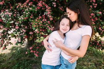 Two girl hugging standing under tree