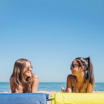 Two girls at the beach talking to each other