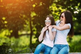 Two girls having fun sitting in park