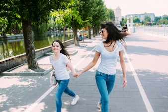 Two girls holding hands walking on pavement