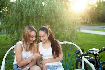 Two girls in a bench looking at their phone