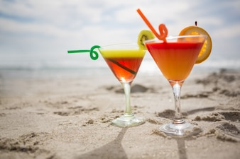 Two glasses of cocktail drink kept on sand
