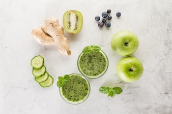 Two green smoothies with ingredients