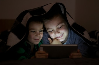 Two kids using tablet pc under blanket at night. Cute Brothers with tablet computer in a dark room smiling.