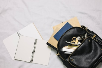 Two netebooks and bag with office supplies