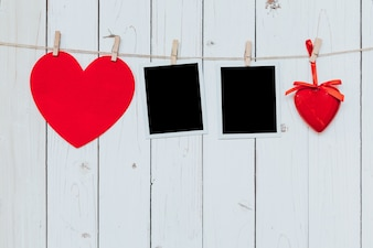 Two photo frame blank and red heart hanging on white wood background with space