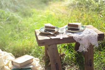 Two pieces of cake on wooden table outdoors