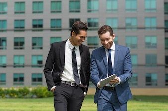 Two Smiling Business Men Using Tablet and Walking