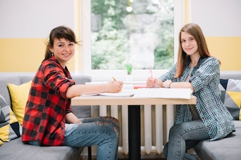 Two smiling girls at desk with textbooks