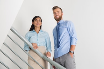 Two Smiling Male and Female Colleagues on Stairs