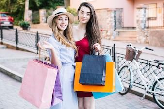 紙袋を持つ2人の笑顔の女性