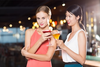 Two Smiling Young Women with Cocktails in Bar