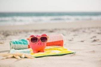 Two starfish and piggy bank with sunglasses on beach blanket