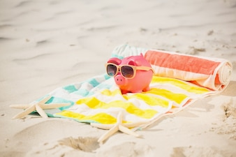 Two starfish and piggy bank with sunglasses on sand