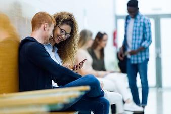 2人の学生が大学で携帯電話を使っています。
