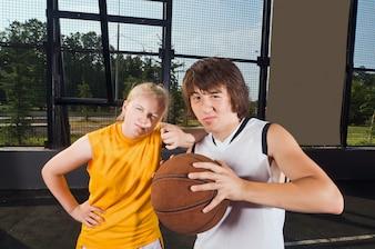 Two teenage basketball players posing