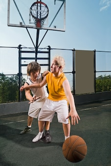 Two teenage players with basketball