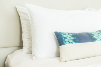 Two white pillows and one blue cushion