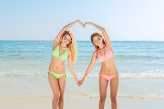Two young asian brunette best friends looking on camera and sending you air kiss, have sexy slim body, wearing bikini sunglasses and fashion bright jewelry, posing in front of tropical beach.