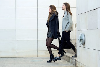 Two young businesswoman walking on the street near office buildi