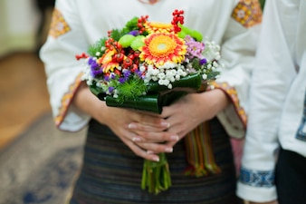 Ukrainian bride in native embroidery holding beautiful colorful autumn bouquet