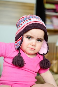 Unhappy baby with hat