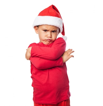 Unhappy child with santa claus hat