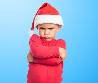Unhappy little boy with blue background