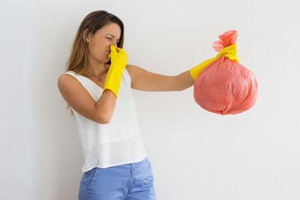 Unhappy woman holding trash with disgusting smell