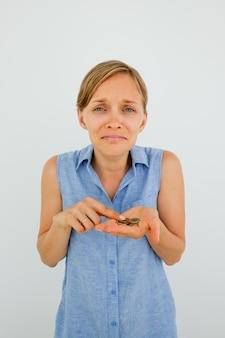 Unhappy Young Woman Counting Coins on Palm
