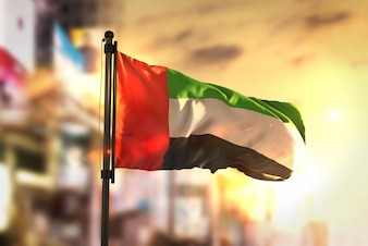 United Arab Emirates Flag Against City Blurred Background At Sunrise Backlight