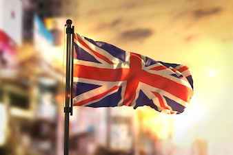 日の出のバックライトで街を曇らせた背景に対する英国の国旗