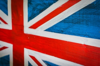 United Kingdom flag painted on aged wooden wall .