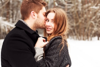 Unshaven guy kissing his cheerful girlfriend